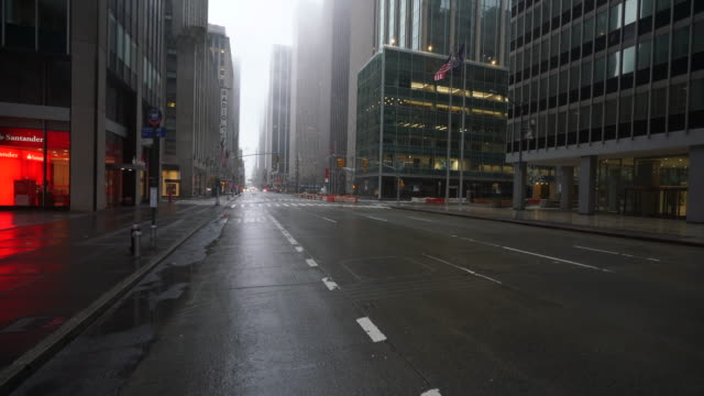 stockvideo's en b-roll-footage met covid-19 effect to new york. people and traffic disappeared from midtown manhattan 6th avenue for impact of covid-19 in the rainy early morning new york city ny usa on mar. 29 2020. - lockdown