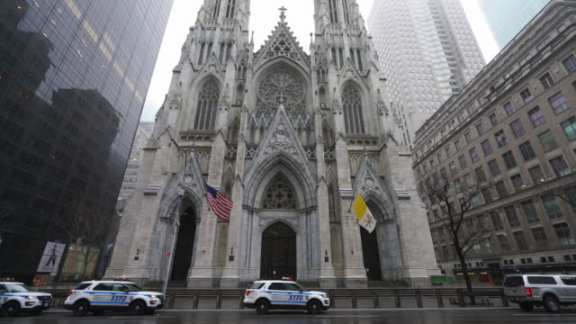 covid-19 effect to new york. people and traffic disappeared from midtown manhattan at front of saint patrick's cathedral for impact of covid-19 in the rainy morning new york city ny usa on mar. 29 2020. - religion stock videos & royalty-free footage