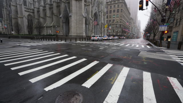 covid-19 effect to new york. people and traffic disappeared from midtown manhattan fifth avenue for impact of covid-19 in the rainy morning new york city ny usa on mar. 29 2020. - ティルト点の映像素材/bロール