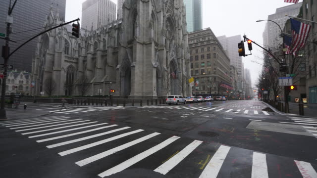 covid-19 effect to new york. people and traffic disappeared from midtown manhattan fifth avenue for impact of covid-19 in the rainy morning new york city ny usa on mar. 29 2020. - crime stock videos & royalty-free footage