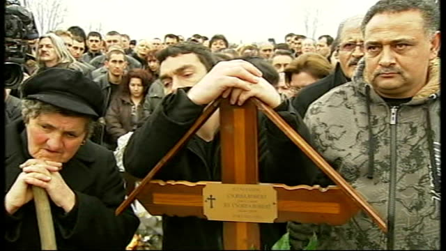 effects of recession on eastern european countries priest saying prayers at graveside mourners at graveside vox pop female mourner sot - mourner stock videos and b-roll footage