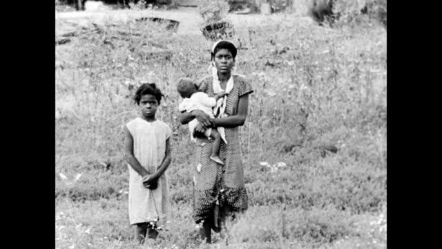 effects of soil erosion down south / dried up tobacco fields / dilapidated farm buildings / african american woman standing in a field with her baby... - dust bowl stock videos and b-roll footage