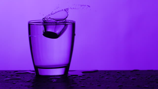 effervescent tablets dissolves in a glass of water - purple background, slow motion - dissolving stock videos & royalty-free footage