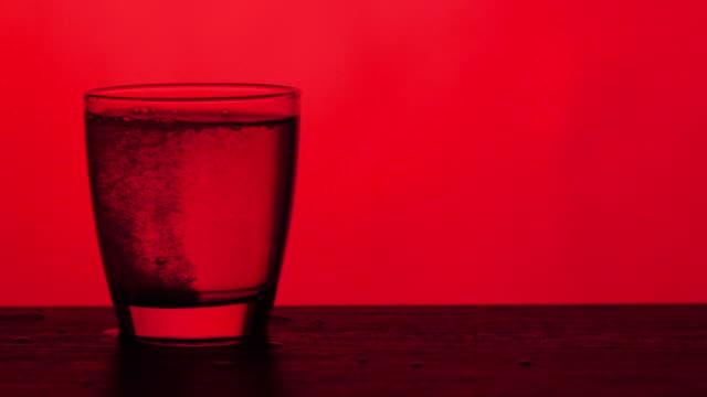vídeos y material grabado en eventos de stock de tabletas efervescentes se disuelve en un vaso de agua - fondo rojo, cámara lenta - disolver