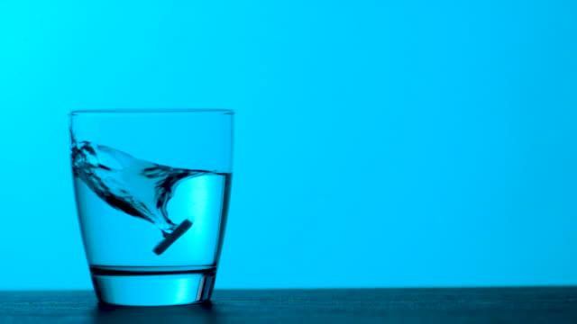 vidéos et rushes de les comprimés effervescents tombent dans un verre d'eau - fond bleu, ralenti - dissolving