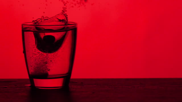 vídeos y material grabado en eventos de stock de tabletas efervescentes caen en un vaso de agua - fondo rojo, cámara lenta - disolver