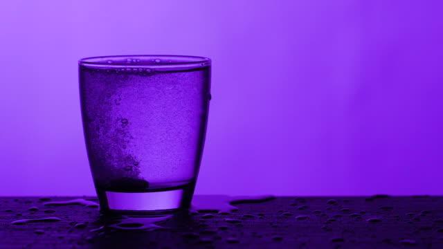 vídeos y material grabado en eventos de stock de tabletas efervescentes en un vaso de agua - fondo azul - disolver