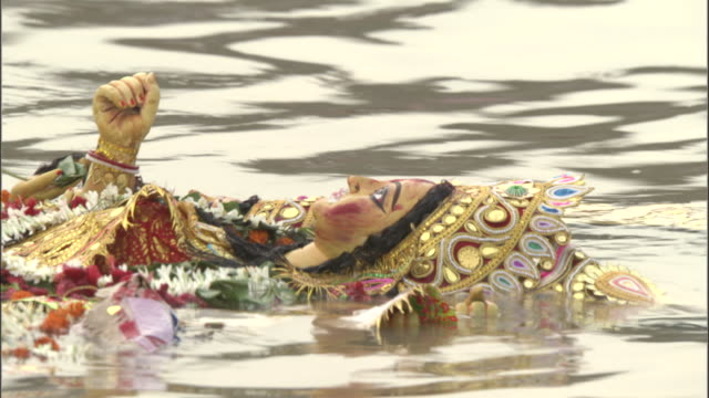 Effigy of Hindu goddess floats along in Hooghly river as part of Durga Puja festival, Kolkata Available in HD.