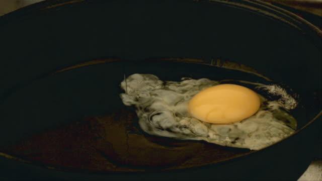 CU SLO MO Egg falling into frying pan / San Francisco, California, USA