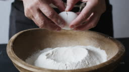 Egg falls on wooden bowl with flour.