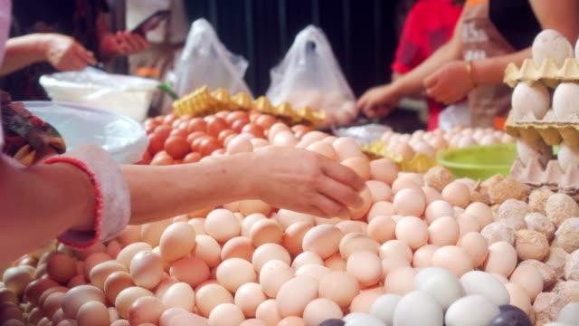 uovo venduto nel mercato alimentare - uovo alimento di base video stock e b–roll