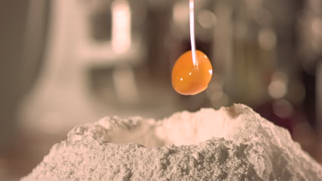 egg yoke falling into pile of flour in kitchen.