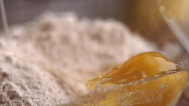 stockvideo's en b-roll-footage met egg yolk being dropped into dry ingredients in mixing bowl banana pancake recipe - volkorentarwe