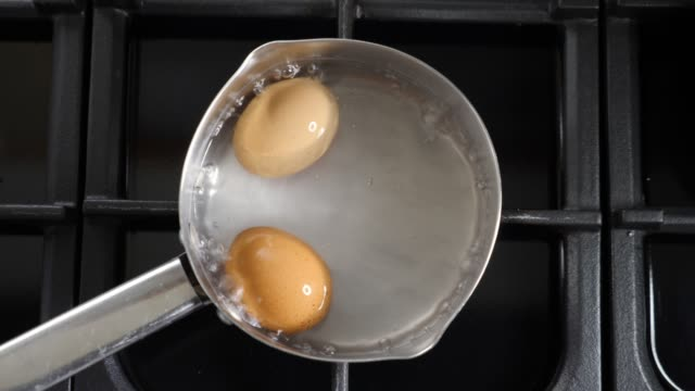 eggs boiling in a saucepan - boiling stock videos & royalty-free footage