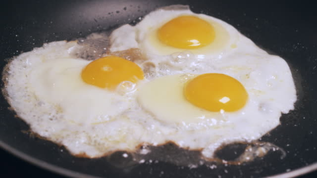 eggs cooking in butter wide