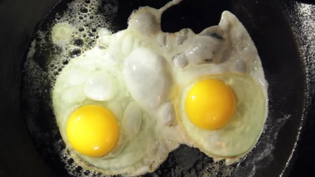 vídeos de stock, filmes e b-roll de eggs frying - skillet cooking pan