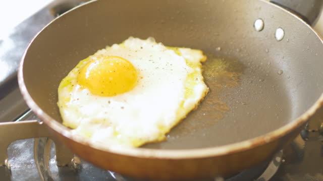 vídeos y material grabado en eventos de stock de huevos en la sartén de cerca - huevos fritos de un solo lado
