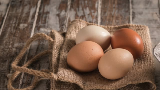 eggs on rustic wooden table - egg stock videos & royalty-free footage