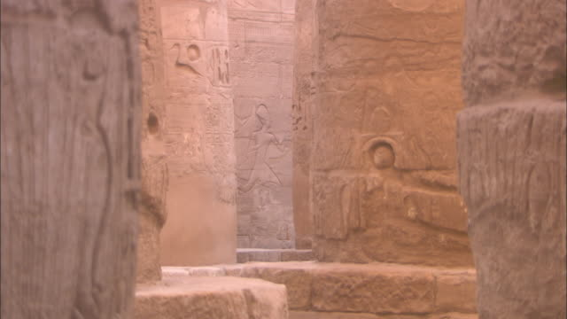 Egyptian carvings and hieroglyphics decorate the ruinous columns of Karnak Temple.