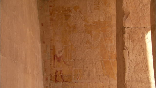egyptian figures are carved on a crumbling stone wall at deir el-bahari egypt. available in hd. - tempio di hatshepsut video stock e b–roll