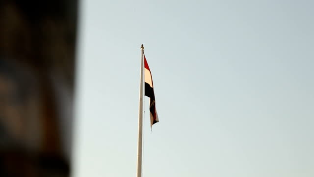 vidéos et rushes de egyptian flag revelaed from behind a wall/ cairo/ egypt - égypte