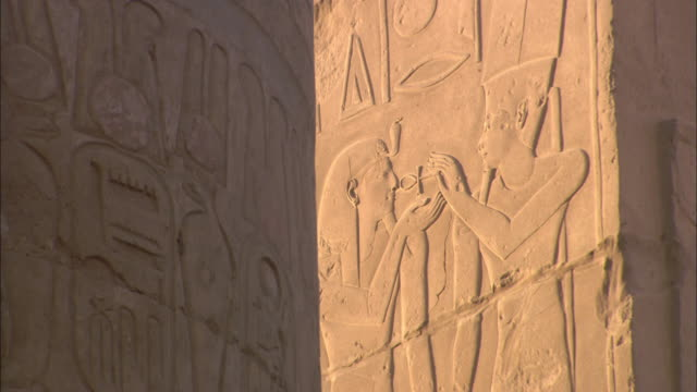 egyptian hieroglyphics and characters decorate the walls of the karnak temple. - temples of karnak stock videos and b-roll footage