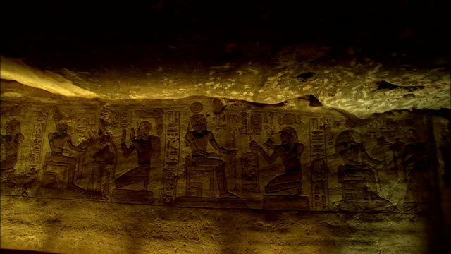 Egyptian hieroglyphs mark the stone wall of the temple of Hathor and Nefertari. Available in HD.
