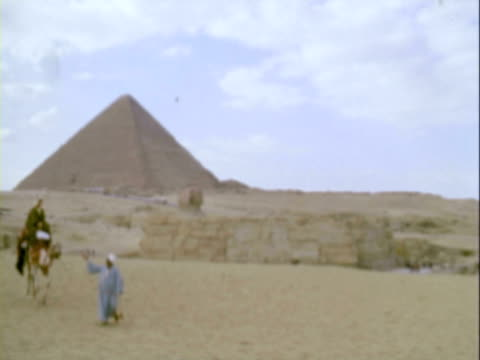 MS Egyptian leading camel with rider past pyramid in desert / Giza, Egypt