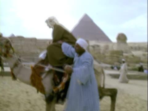 vídeos de stock e filmes b-roll de ms egyptian man helping woman onto camel / giza, egypt - 1960
