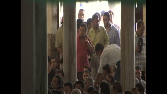vidéos et rushes de egyptian men file through an entrance into a room full of seated men. - fidèle religieux