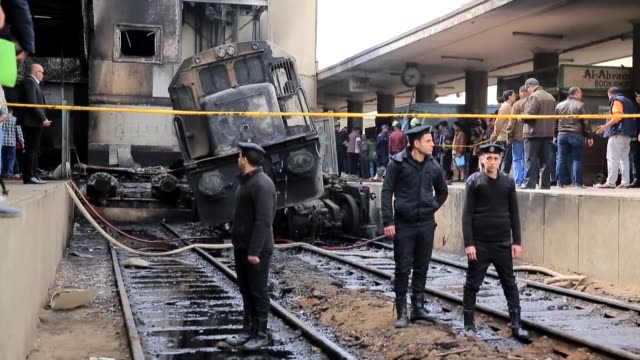 Egyptian officials work at the site of a fiery train crash at the Ramses train station in Cairo Egypt on February 27 2019 At least 25 people were...