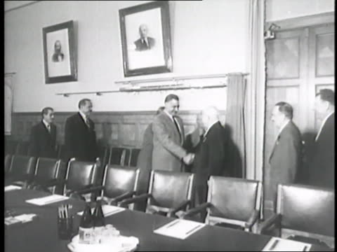 Egyptian President Gamal Abdal Nasser and Soviet Premier Nikita Khrushchev shake hands in a conference room while meeting for the formation of the...