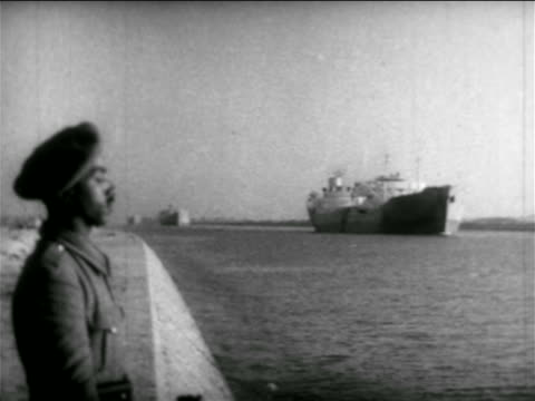 vídeos de stock e filmes b-roll de egyptian soldier standing on shore of suez canal with freighter in background / egypt / suez canal - 1956
