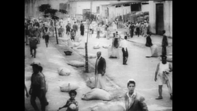 vídeos de stock e filmes b-roll de / egyptians cities and towns under attack / egyptian civilians milling about chaotically on the streets / united nations in new york vote for... - 1956