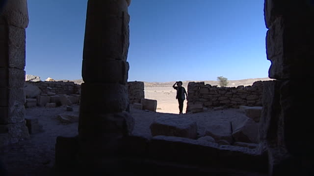 egyptologist and author david rohl walks into the temple of seti i in wadi kanais in egypt's eastern desert. - back lit video stock e b–roll