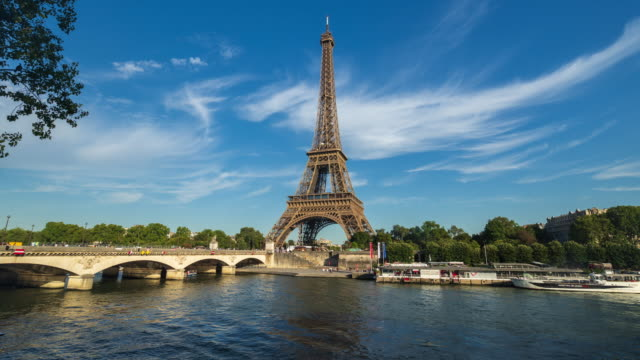 eiffel tower and river seine with blue sky - 4k time-lapse - river seine stock videos & royalty-free footage