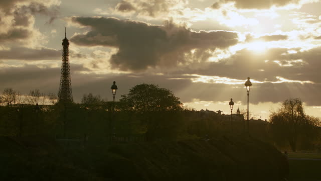 WS Eiffel Tower in the distance during sunset, public park in foreground / Paris, France