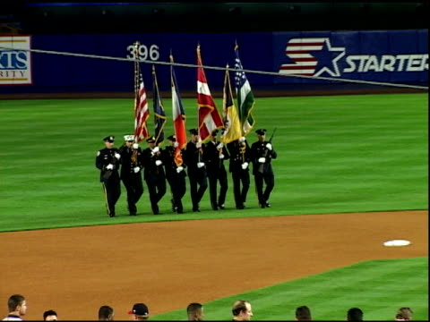 zo eight uniformed nypd nyfd members walk on field in opening ceremony at shea stadium carrying us other flags at first baseball game after september... - shea stadium stock videos and b-roll footage