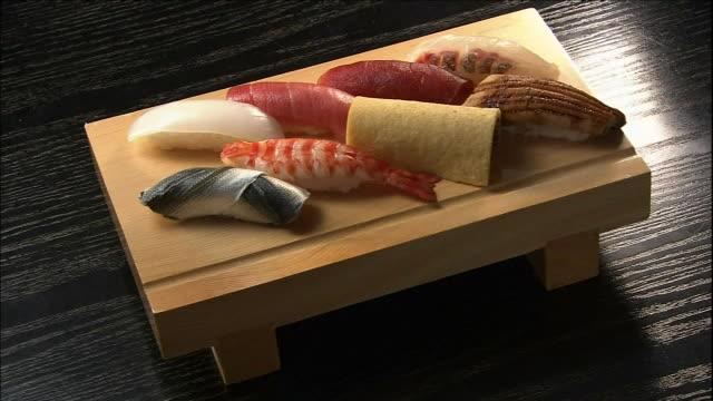 eight varieties of nigiri ovals sit on a sushi board. - nigiri stock videos and b-roll footage