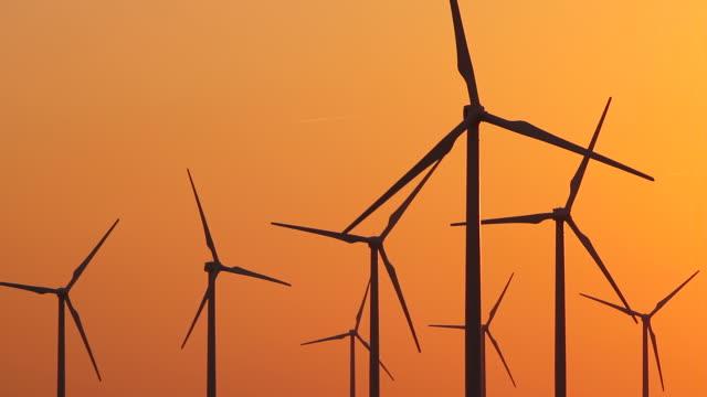 Eight Wind Turbines Orange Sky With Jet