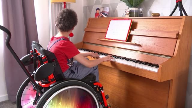 eight year old cerebral palsy sufferer lennie street plays piano to raise money for his school; england: int lennie street speaking and playing piano... - cerebrum video stock e b–roll
