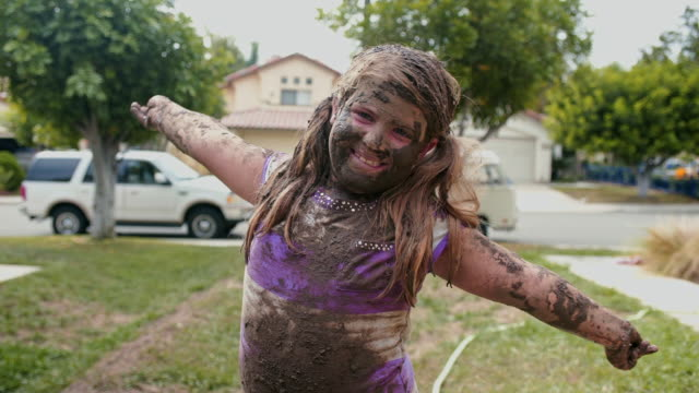 eight year old girl, arms in the air, covered in mud - mud stock videos & royalty-free footage
