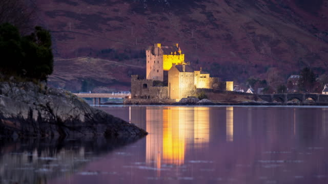 eilean donan castle illuminated at dusk - time lapse - loch duich stock videos & royalty-free footage