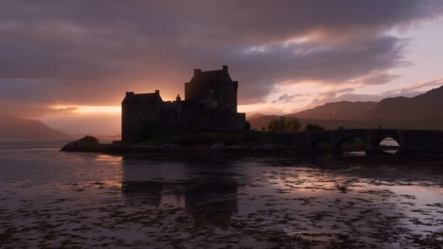 eilean donan castle reflecting in loch duich at sunset, scottish highlands. eilean donan castle, dornie, loch duich, scottish highlands, scotland, uk. - atmospheric mood stock videos & royalty-free footage