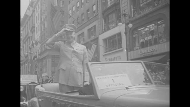 eisenhower riding in car in parade in nyc at end of wwii waving to crowds passing under the washington square arch tipping his cap ticker tape falls... - end cap stock videos & royalty-free footage