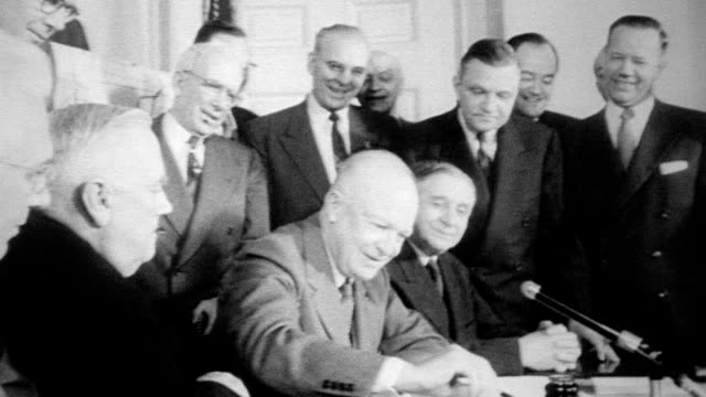 eisenhower seated at desk signing st lawrence seaway bill while surrounded by various dignitaries and members of the government / three men sit down... - north atlantic ocean stock videos & royalty-free footage