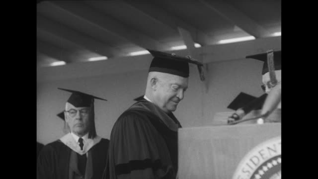 stockvideo's en b-roll-footage met vs eisenhower stands next to a lectern removes mortarboard / vs he smiles as he holds a replica nittany lion - afstudeer toga