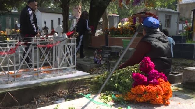el olor a cera fundida se mezcla con el aroma de las flores de cempasuchil colocadas sobre las tumbas que albergan los cementerios mexicanos donde... - día stock videos & royalty-free footage