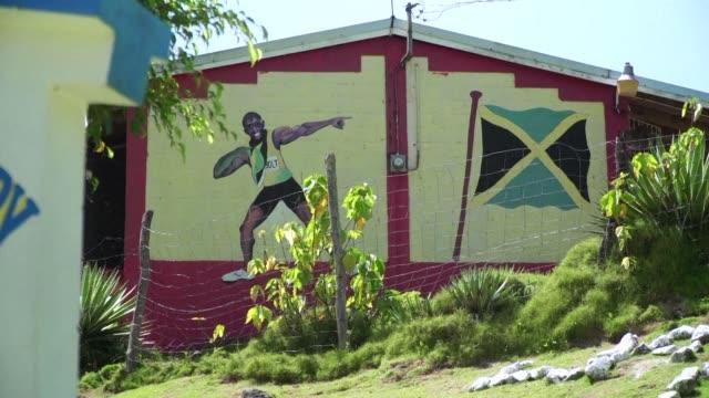 stockvideo's en b-roll-footage met el recorrido de usain bolt de nino del campo a medallista olímpico y heroe global del deporte tiene sus raices en una remota villa de jamaica:... - jamaica