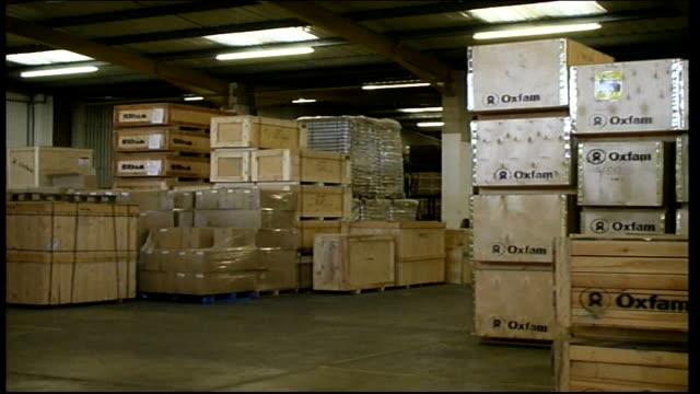 vídeos y material grabado en eventos de stock de el salvador earthquake: oxfam aid shipment in warehouse; england: oxfordshire: oxford: int wooden box with word 'oxfam' on it pull out to boxes on... - paleta herramientas industriales